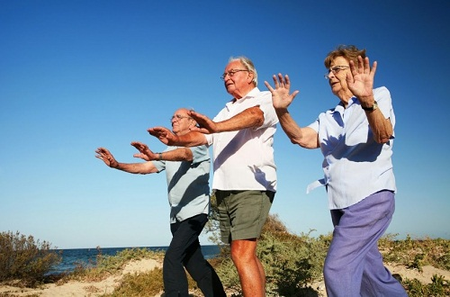 Three seniors doing tai chi on the beach